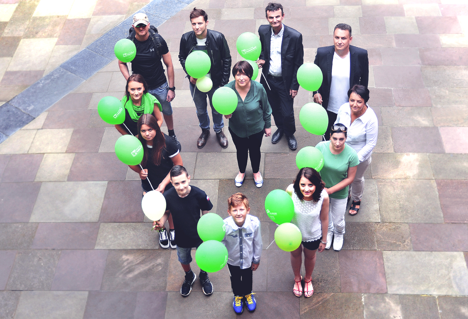 Grupa podopiecznych Fundacji wraz z Urszulą Smok. Osoby ustawione są w kształt serca. W rękach trzymają zielone balony