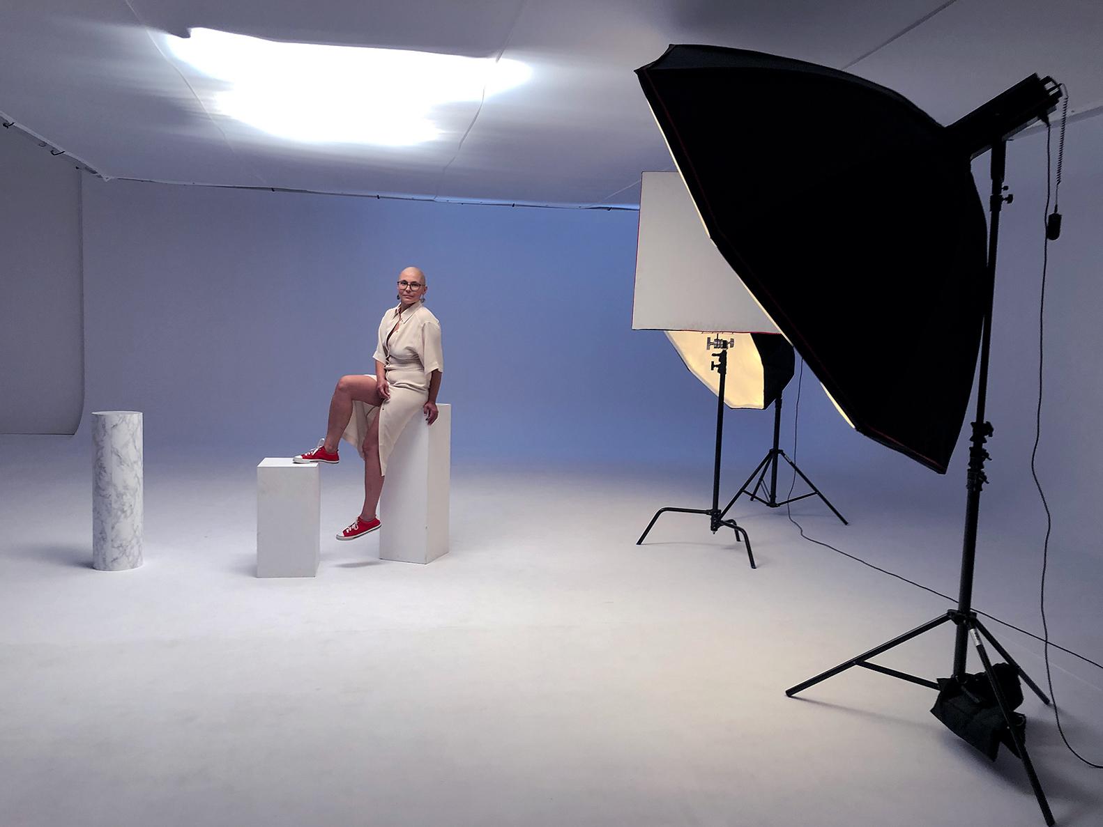 Studio fotograficzne, widoczne lampy fotograficzne. W głębi na podeście siedzi kobieta bez włosów, w długiej, jasnej sukience i czerwonych trampkach. Lewą nogę trzyma oparta o mniejszy podest przed sobą