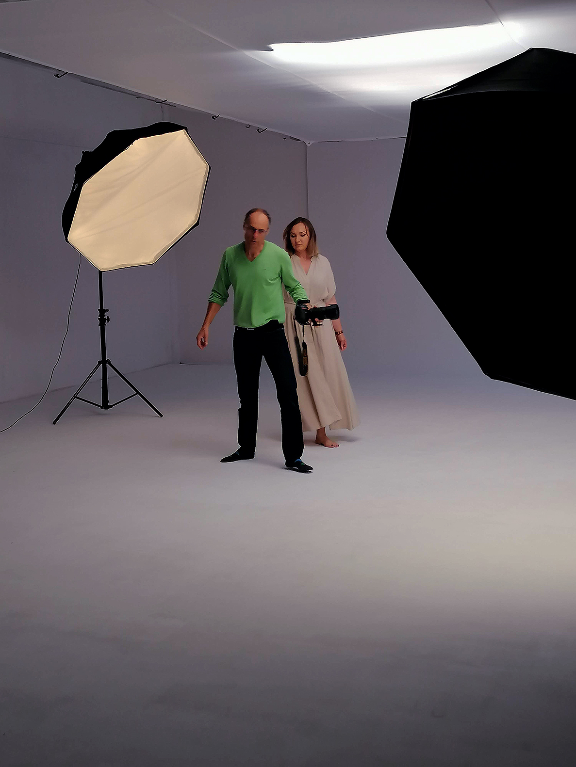 Kobieta i mężczyzna na planie fotograficznym pośród lamp. Mężczyzna trzyma aparat i pokazuje kobiecie ruch. Ona ubrana w długą, jasną sukienkę, przygląda mu się.