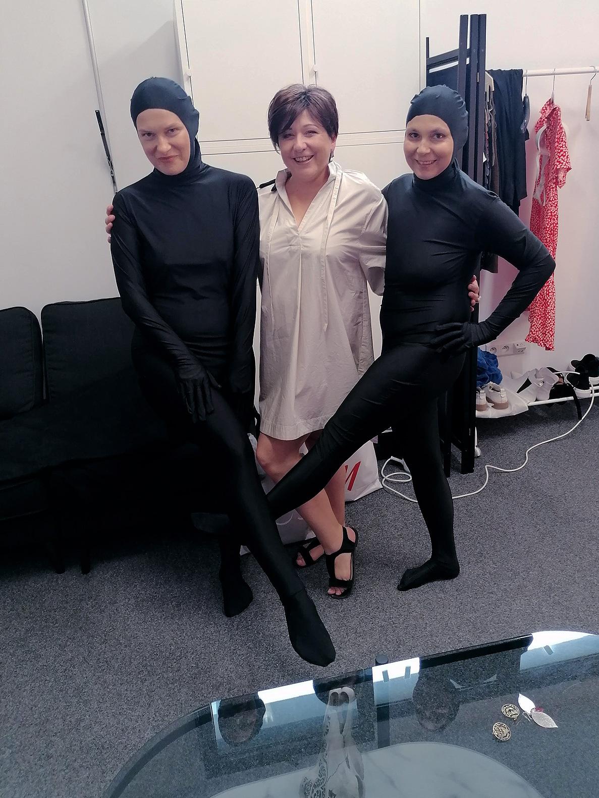 Trzy uśmiechnięte kobiety ustawione w jednej linii. Dwie z nich, po bokach, ubrane są od stóp do głów w czarny, jednolity, przylegający do ciała kostium. w środku stoi Urszula Smok w jasnej sukience prze kolano