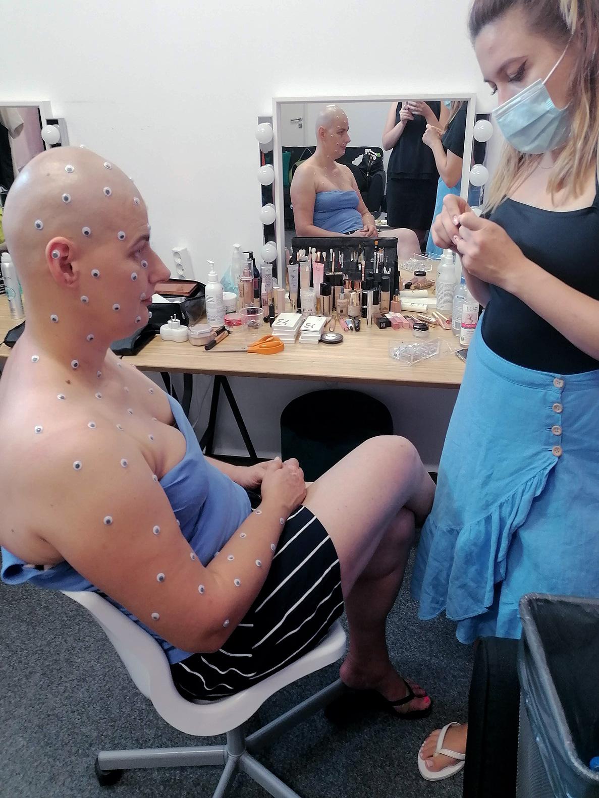 Garderoba, w tle lustro. Na pierwszym planie kobieta bez włosów, w bluzce bez ramiącek, na głowie, twarzy, ramionach i dekolcie ma przyklejone naklejki w kształcie oczu. Obok stoi makijażystka w maseczce.