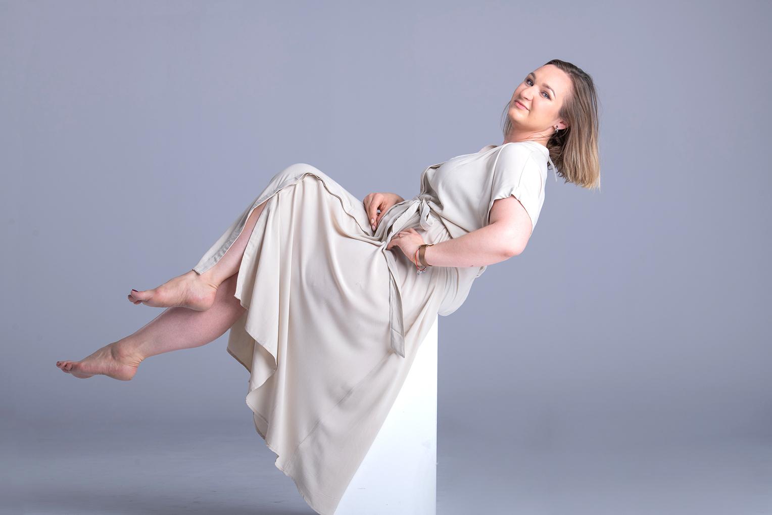 Kobieta wzwiewnej sukience siedzi napostumencie, zzałożonymi nogami. Delikatnie odchyla się dotyłu